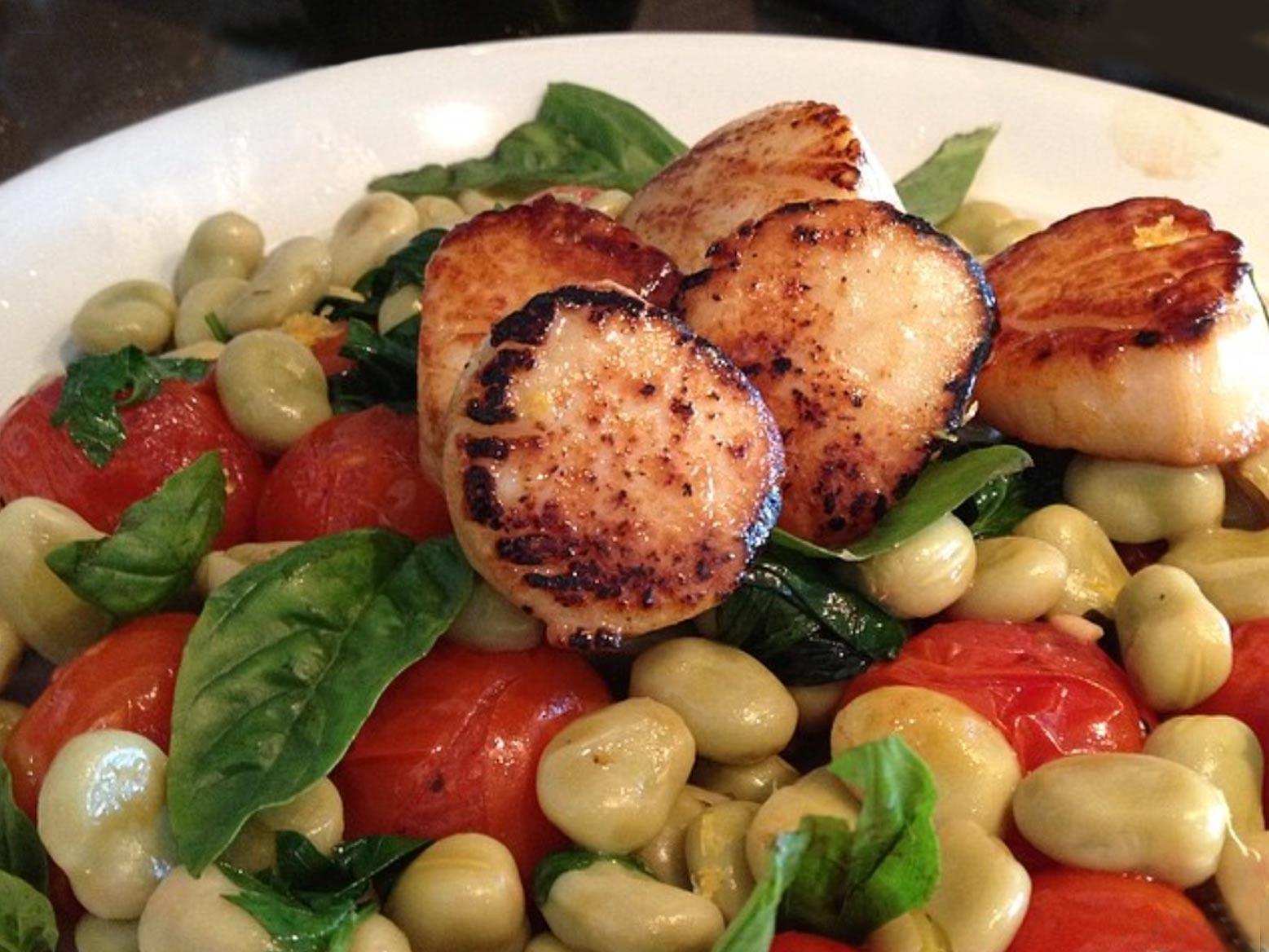 Grilled scallops on plate with vegatables.