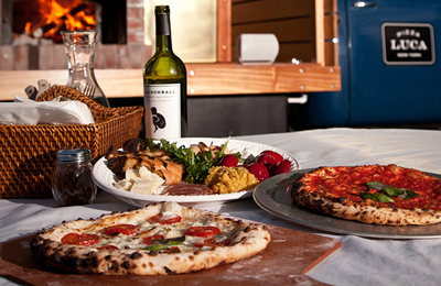 Three pizza pies and glass of wine on table.