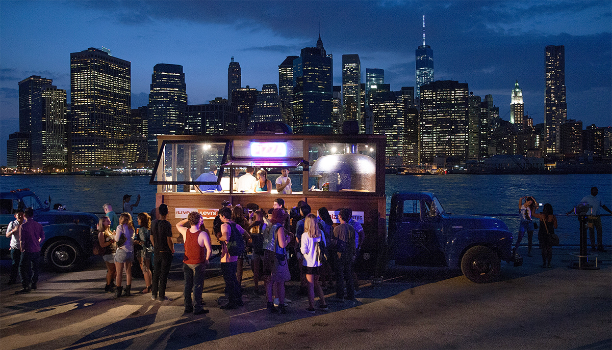 Pizza truck doing business at night with NYC skyline behind it.