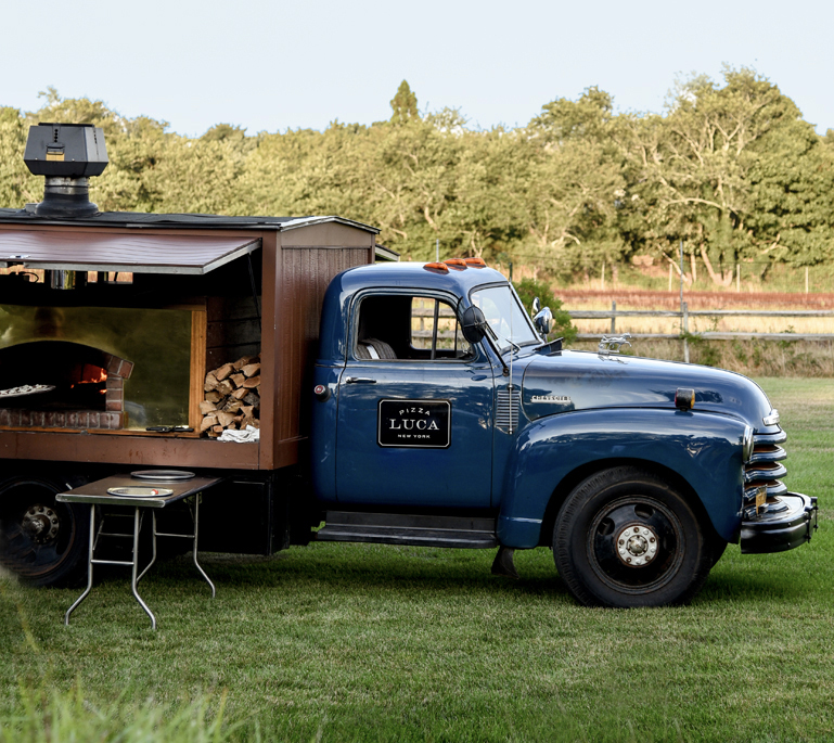 Pickup truck with pizza oven on back, open with wood burning.