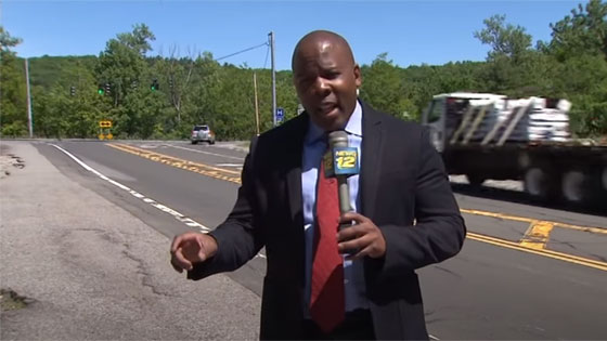 Reporter talking on camera along the side of the road.